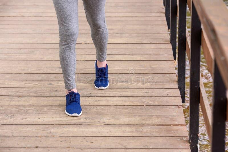 kantjusterad sikt av idrottskvinnan, i att gå för gymnastikskor arkivbilder