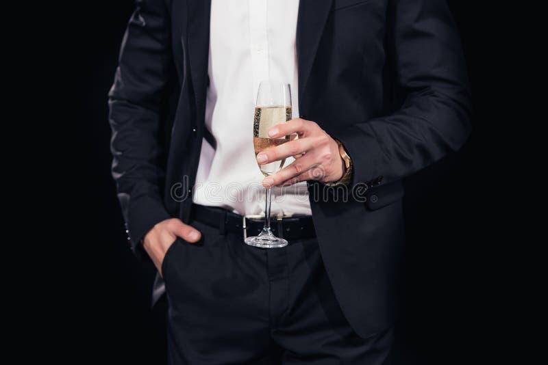 kantjusterad sikt av mannen i dräkt med handen i facket som rymmer exponeringsglas av champagne isolerat royaltyfri bild