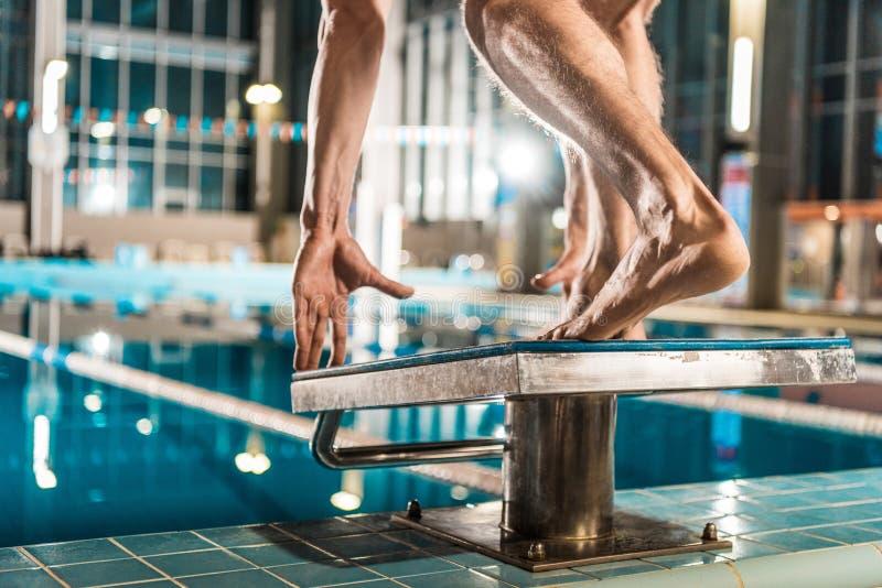 kantjusterad sikt av simmareanseendet på dykningbrädet som är klart att hoppa in i konkurrens arkivbild