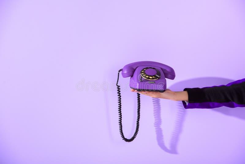 kantjusterad sikt av telefonen för hållande tappning för flicka den roterande på den ultravioletta väggen arkivbild