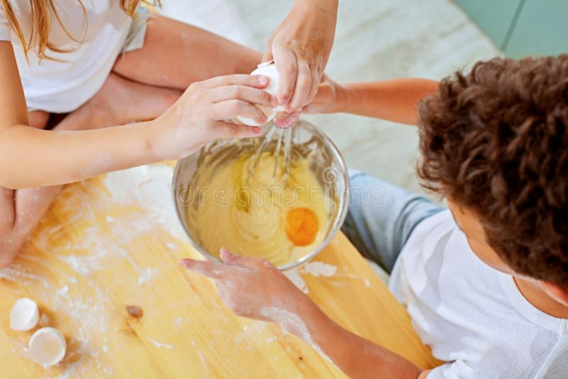 Kantjusterad sikt av ungen som tillfogar ägg för att pudra i exponeringsglasbunke royaltyfri fotografi