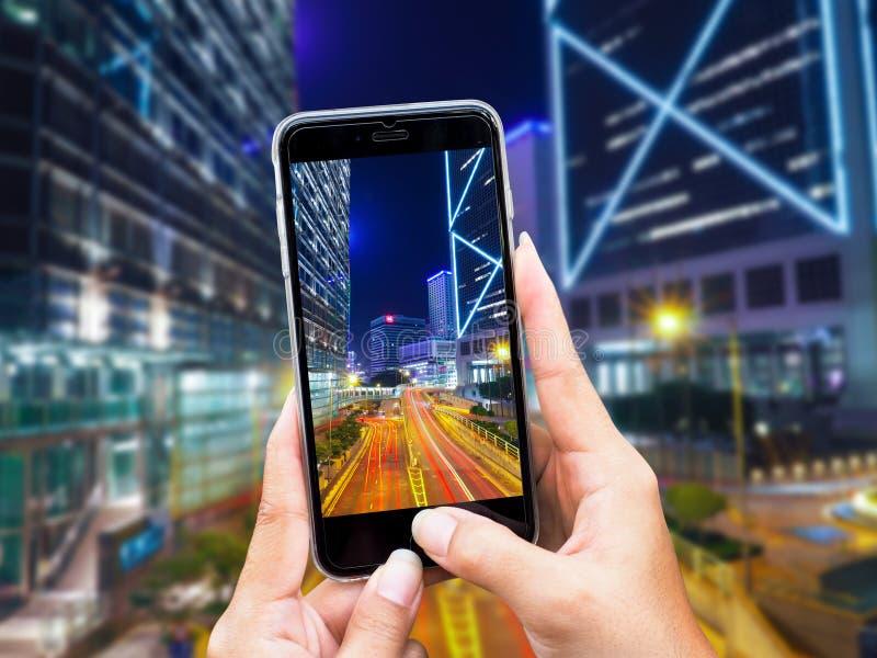 Kantjusterad skjuten sikt av kvinnas händer som gör fotoet på mobiltelefonkamera av byggnad på natttrafik i Hong Kong City royaltyfri foto