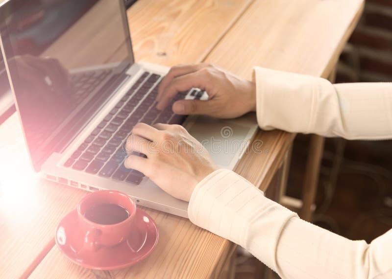 Kantjusterad skottsikt av kvinnan som arbetar på bärbar datordatoren medan sitt royaltyfri fotografi