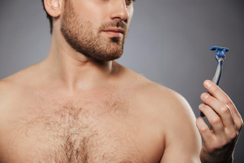 Kantjusterad stående av den nakna mannen med borstet som ser rakknivhållen arkivfoto