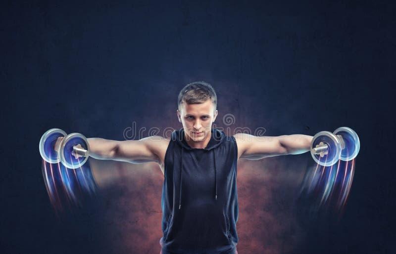 Kantjusterad stående av en konditionman som gör sidolönelyft med hantlar fotografering för bildbyråer