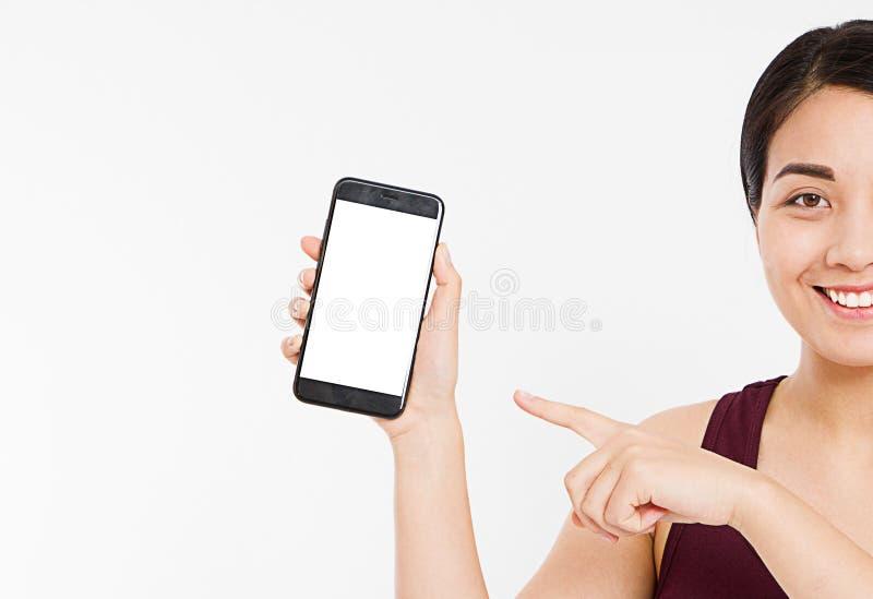 Kantjusterad ståendeasiat, koreansk kvinna, mobiltelefon för tom skärm för flickahåll, peka för finger som isoleras på vit bakgru royaltyfri foto