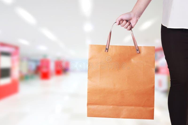 Kantjusterad ståendebild av den unga damen som rymmer shoppingpåsen över suddig bakgrund för galleriamarknadslager fotografering för bildbyråer