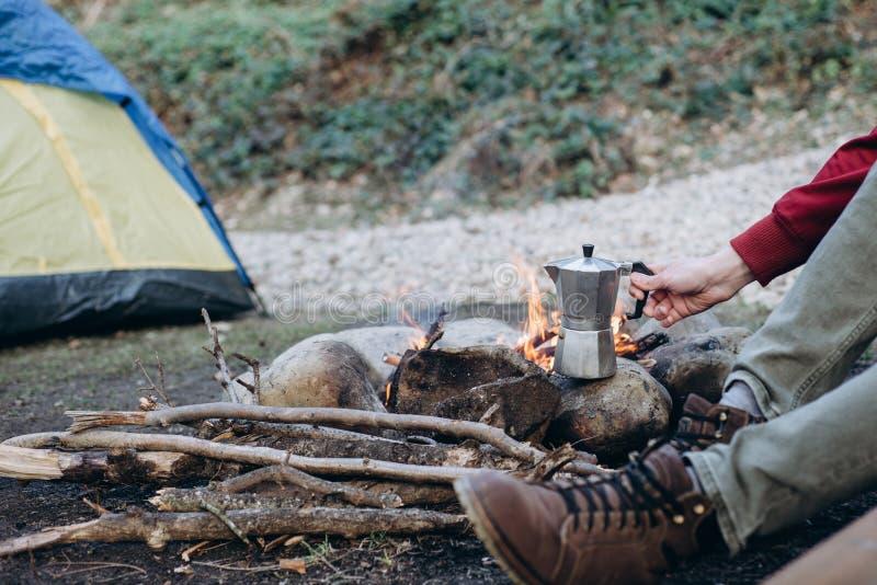 Kantjusterad utomhus- bild av utforskaren för ung man som förbereder den varma drycken i berg arkivbild