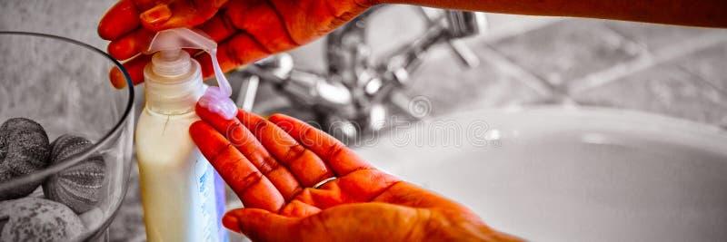 Kantjusterade händer genom att använda tvålutmataren i badrum royaltyfri foto