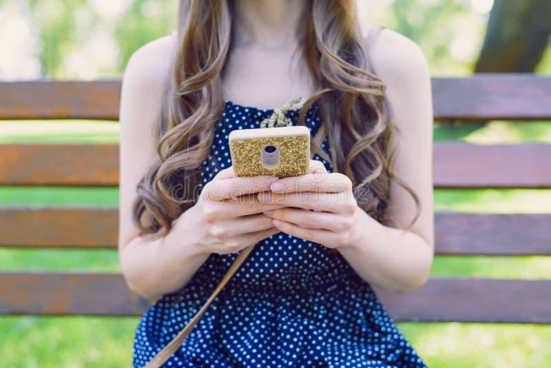 Kantjusterat closeupfoto av den slanka älskvärda nätta attraktiva tonåriga telefonen för damanvändareinnehav i guld- fall, i att  arkivbild