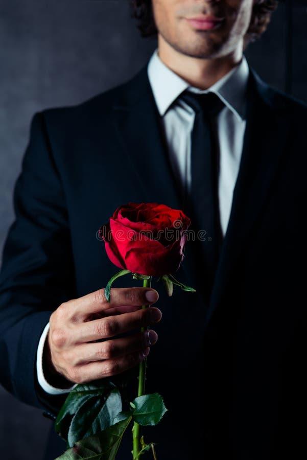 Kantjusterat foto av affärsmannen som rymmer en röd ros i hans hand Honom royaltyfri foto
