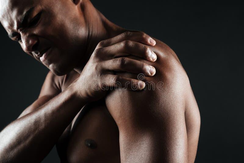 Kantjusterat foto av den unga shirtless afro amerikanska mannen med skuldran royaltyfri foto