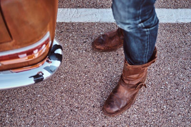 Kantjusterat foto av en man i jeans och kängor som står nära den retro bilen i stadsparkeringen royaltyfri fotografi
