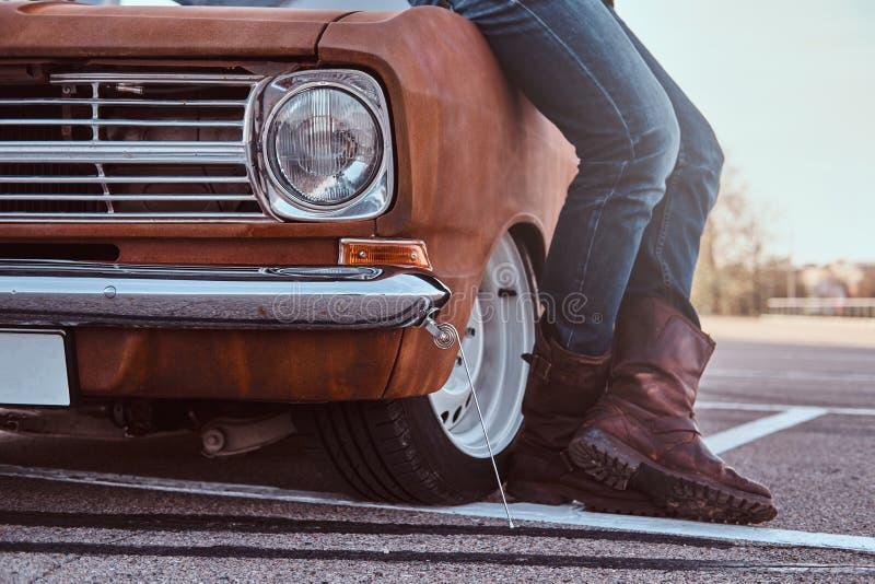 Kantjusterat foto av manligt i jeans och kängor som lutar på den retro bilen i stadsparkeringen royaltyfria foton