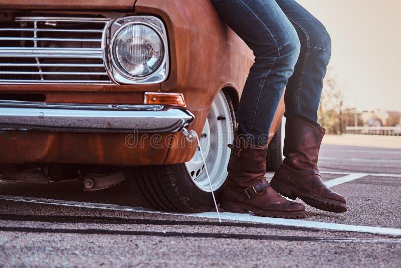 Kantjusterat foto av manligt i jeans och kängor som lutar på den retro bilen i stadsparkeringen royaltyfri bild