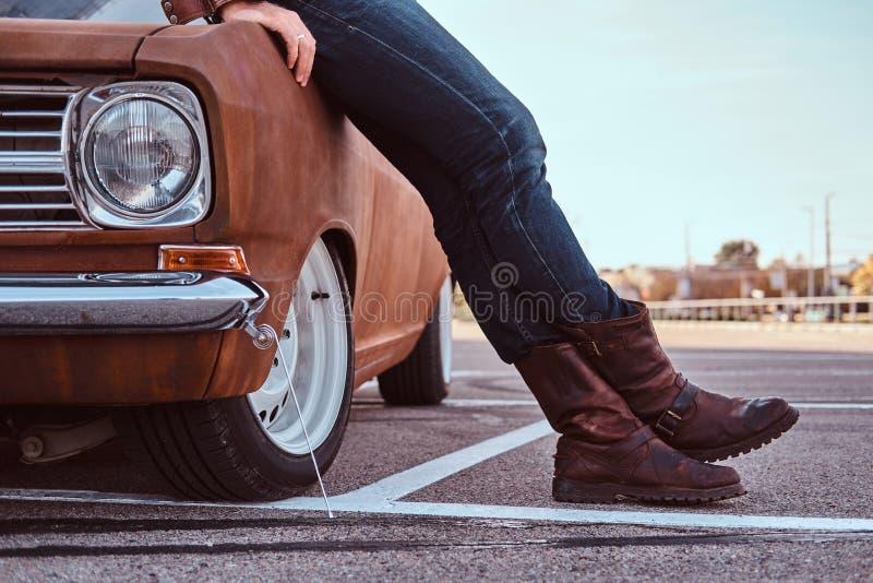 Kantjusterat foto av manligt i jeans och kängor som lutar på den retro bilen i stadsparkeringen arkivbilder