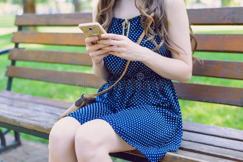 Kantjusterat sidoprofilslut upp fotoet av en charmig telefon för användaredaminnehav i det guld- fallet som lämnar återkopplingar arkivfoto