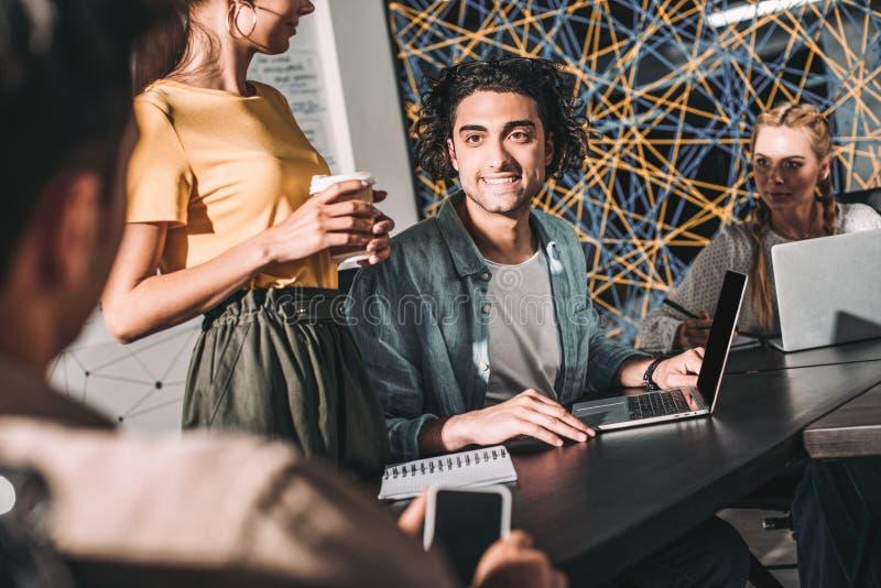 kantjusterat skott av affärskollegor som har möte på tabellen med bärbara datorer i modernt royaltyfria bilder
