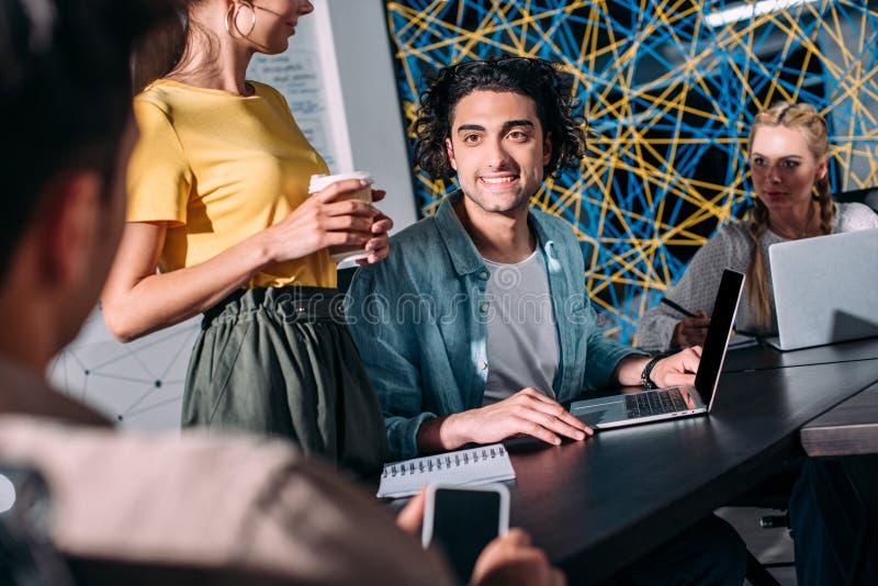 kantjusterat skott av affärskollegor som har möte på tabellen med bärbara datorer i modernt royaltyfria foton