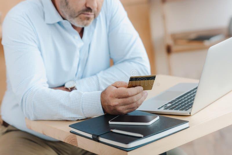kantjusterat skott av affärsmannen som gör e-shopping arkivbild