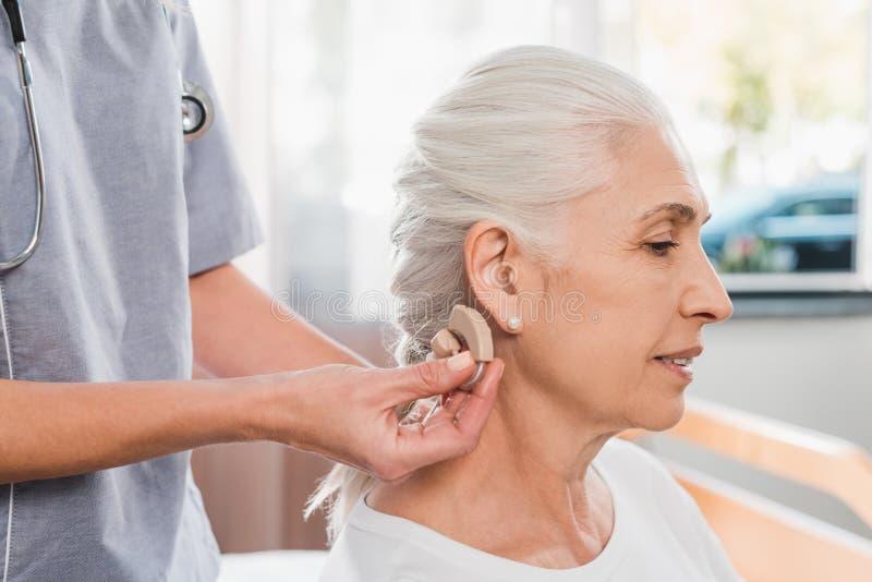 kantjusterat skott av bärande hörapparat för sjuksköterska till royaltyfri foto