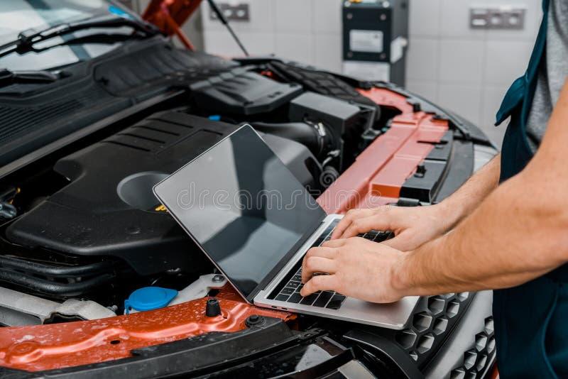 kantjusterat skott av den automatiska mekanikern som arbetar på bärbara datorn med den tomma skärmen på bilen med den öppnade bil arkivbild