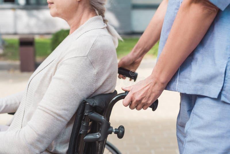 kantjusterat skott av den driftiga rullstolen för sjuksköterska fotografering för bildbyråer