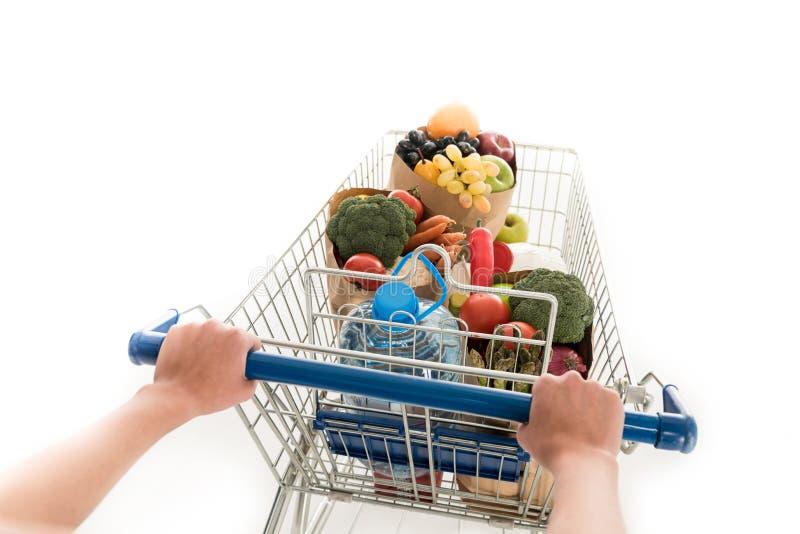 kantjusterat skott av den driftiga shoppingspårvagnen för kvinna med livsmedelsbutikpåsar och den plast- flaskan av vatten royaltyfri bild