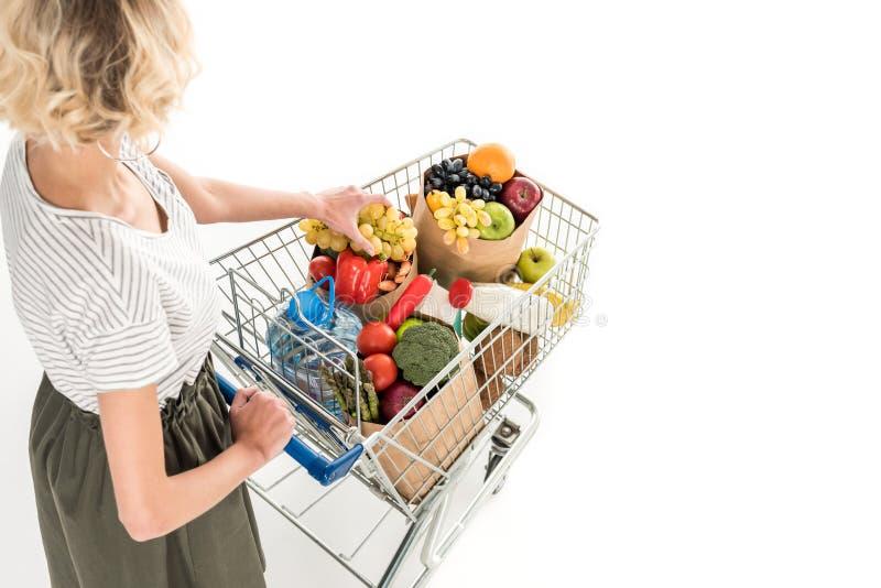 kantjusterat skott av den driftiga shoppingspårvagnen för ung kvinna med livsmedelsbutikpåsar och den plast- flaskan av vatten arkivbilder