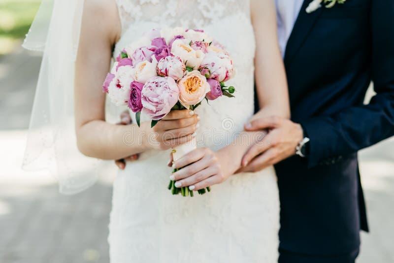 Kantjusterat skott av den härliga bruden i den hållande buketten för vit bröllopsklänning som står nära brudgummen som kramar hen royaltyfri fotografi