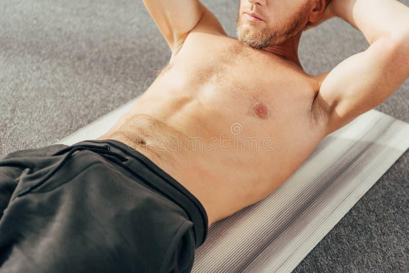 kantjusterat skott av den shirtless mannen som gör abs för att öva på matt yoga royaltyfri bild