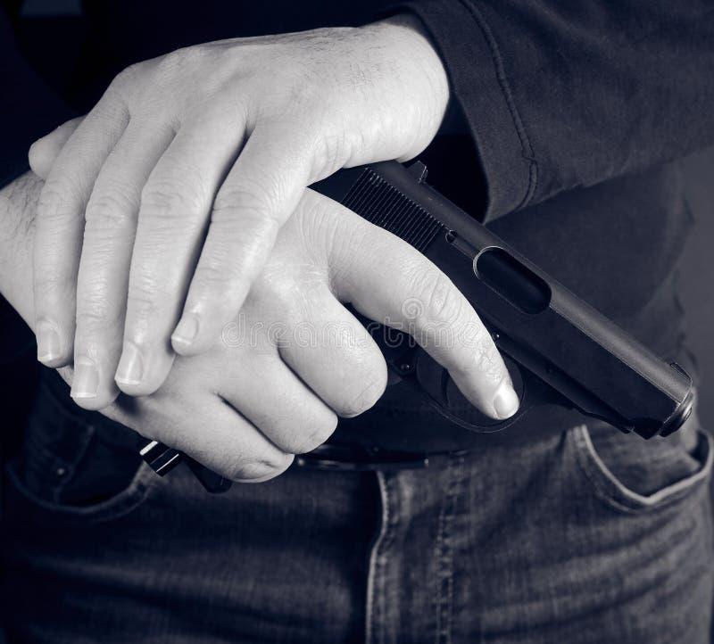 Kantjusterat skott av det hållande vapnet för man i hand royaltyfri bild