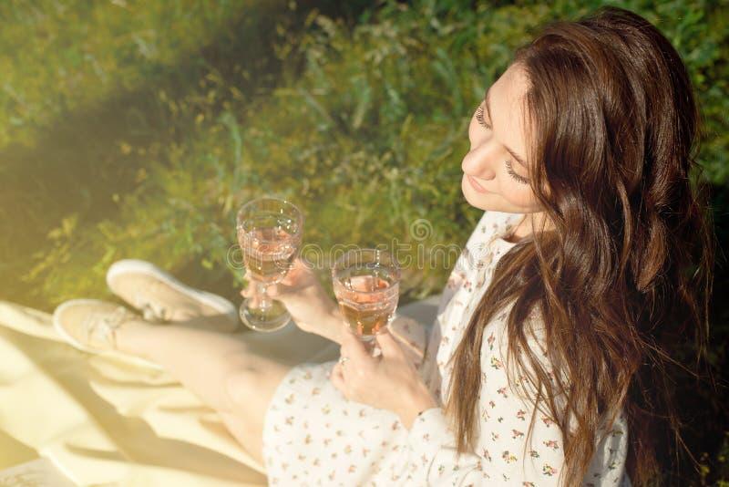 Kantjusterat skott av en flicka, i en sommarkl?nning som sitter med ett exponeringsglas av vin p? en picknick, medan tycka om p?  arkivbild