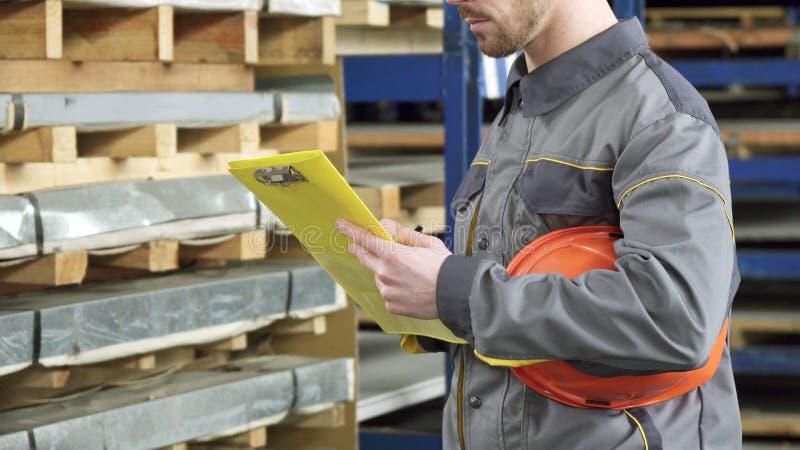 Kantjusterat skott av en lagerarbetare som kontrollerar inventarium i materiel royaltyfria foton