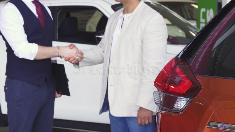 Kantjusterat skott av en man som skakar händer med bilåterförsäljaren royaltyfri fotografi