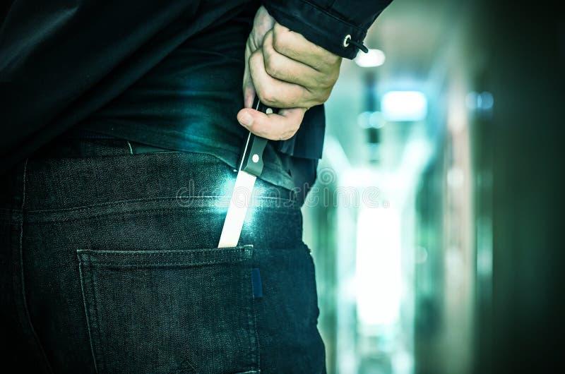 Kantjusterat skott av en personnederlaghand - gjord kniv bak hans baksida royaltyfria foton