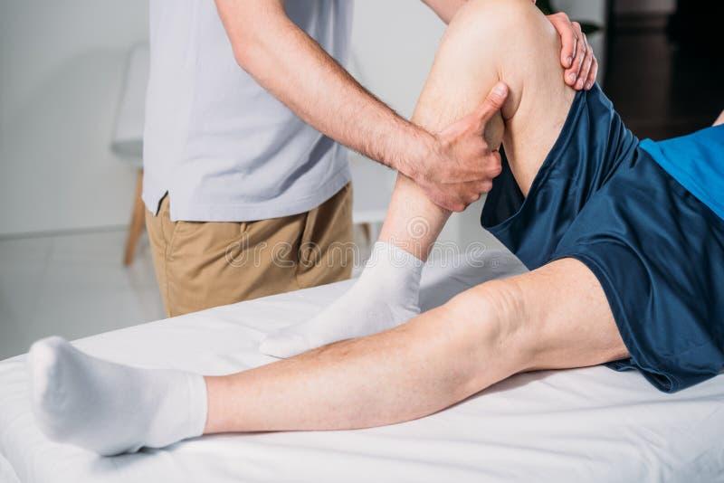 kantjusterat skott av fysioterapeuten som gör massage till den höga mannen arkivbilder
