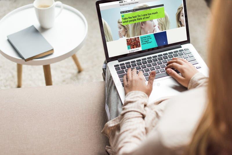 kantjusterat skott av hemmastatt sammanträde för kvinna på soffan och användabärbara datorn med bbc royaltyfri fotografi