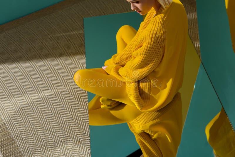 kantjusterat skott av kvinnan i gul tröja och strumpbyxor som sitter på spegeln med reflexion arkivbild