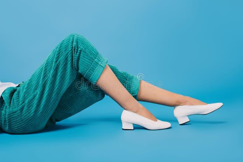 kantjusterat skott av kvinnan i stilfulla flåsanden och skor som ligger på golv fotografering för bildbyråer