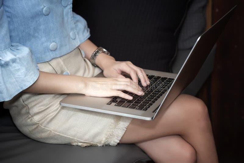 kantjusterat skott av kvinnan som använder bärbara datorn på knä royaltyfri foto