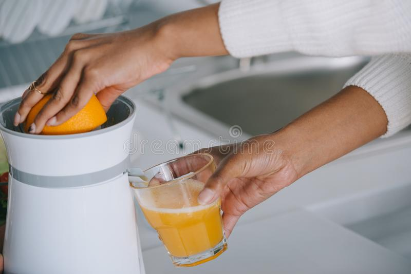 kantjusterat skott av kvinnan som pressar ny orange fruktsaft arkivfoto
