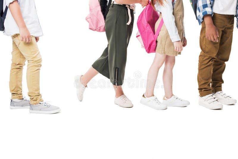 kantjusterat skott av multietniska barn med ryggsäckar som står tillsammans isolerade på vit arkivbild
