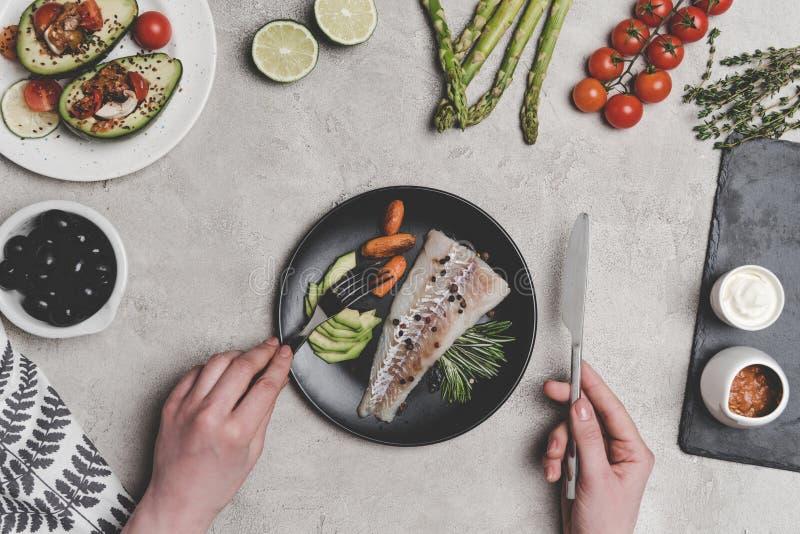 kantjusterat skott av personen som äter fisken med sunda grönsaker på grå färger arkivbilder