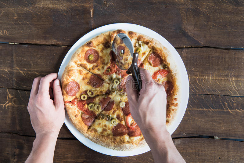 Kantjusterat skott av personen som klipper läcker ny pizza royaltyfri foto