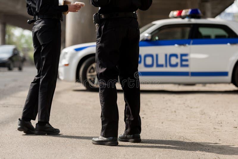 kantjusterat skott av poliser som framme står av arkivfoto