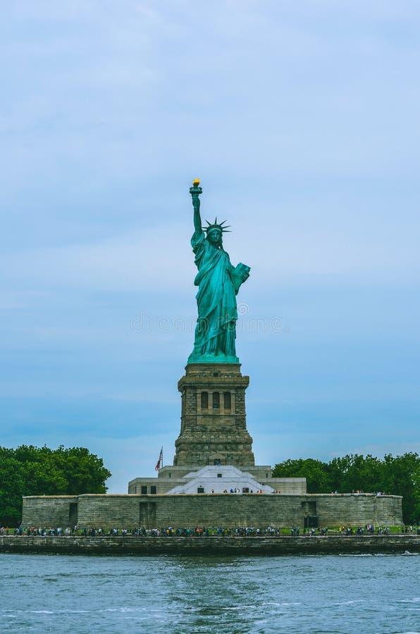 Kantjusterat skott av statyn av frihet med vatten och himmel arkivfoton