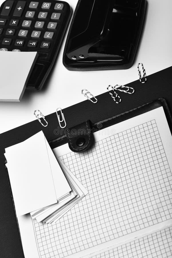Kantoorbehoeften en leer behandeld notitieboekje met blanco pagina's Bedrijfs en het werkconcept: bureauhulpmiddelen op zwart-wit royalty-vrije stock fotografie