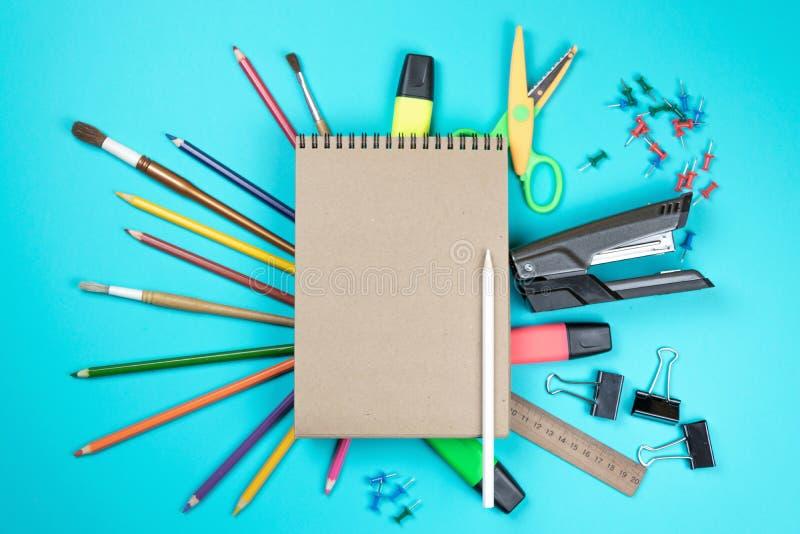 Kantoorbehoeften kleurrijke die het schrijven de pennenpotloden van hulpmiddelentoebehoren, Kraftpapier-document op blauwe achter stock foto