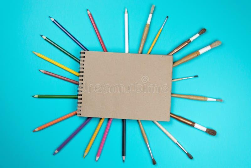 Kantoorbehoeften kleurrijke die het schrijven de pennenpotloden van hulpmiddelentoebehoren, Kraftpapier-document op blauwe achter stock fotografie